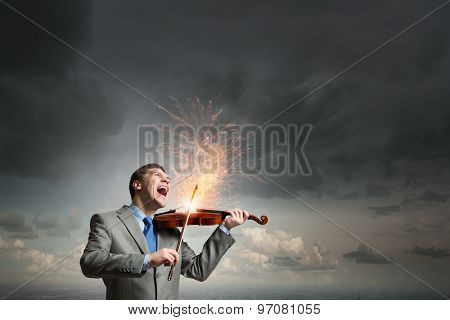 Young emotional businessman playing with passion violin instrument