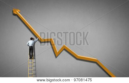 Businessman standing on ladder and reaching growing graph