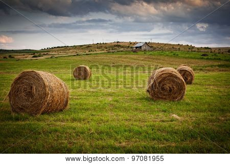 hay bales on meadow and small farm against sunset background