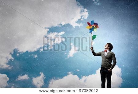 Young happy businessman with colorful windmill in hand
