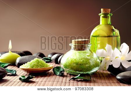 Bath Salts And Oil With Flowers And Stones Brown Background
