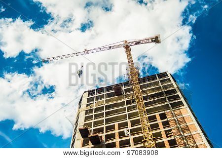 Tall building construction and crane under a blue sky