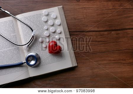 Stethoscope on book with pills  on wooden background