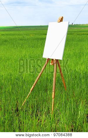 Easel with canvas in green field