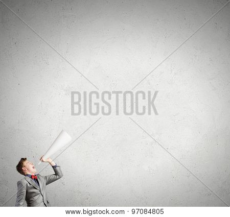 Young man making some announcement in trumpet