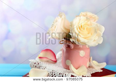 Fresh roses with old book and letters on color wooden table, on light background. Vintage concept
