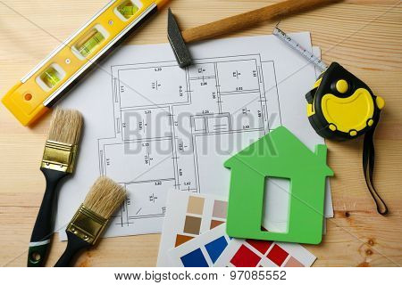 Construction instruments, plan and brushes on wooden table background