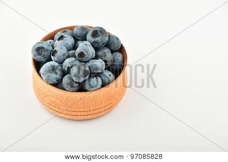 Handful Of Blueberries In Wooden Bowl Isolated On White