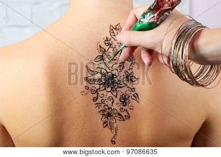 Process of applying Mehendi on female back, close up