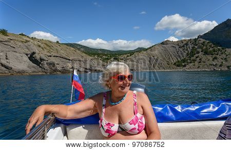 Senior Lady Is In Sea Boat On Cliffs Background, Crimea.