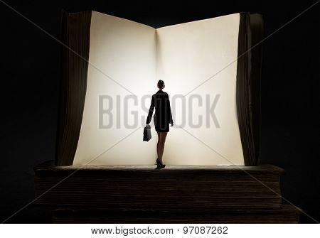 Big old opened book and miniature of businesswoman