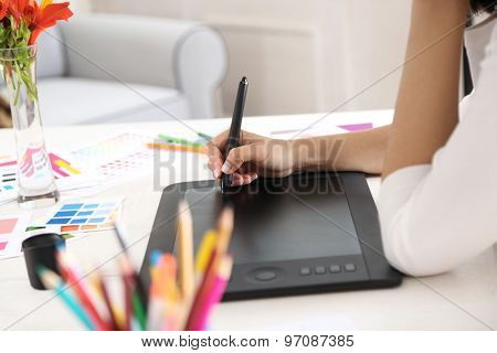 Artist drawing on graphic tablet in office