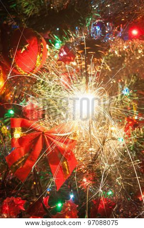 Burning sparkler on a decorated Christmas tree