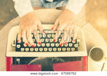Woman Typing On A Typewriter With Cup Of Coffee