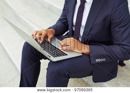 Contemporary businessman typing on laptop keypad