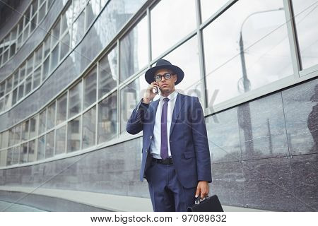 Young man in suit, hat and eyeglasses speaking on the phone while standing by modern building