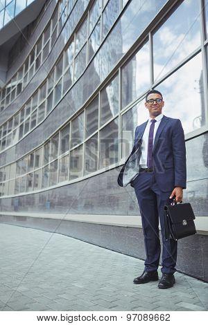 Happy businessman in formalwear standing by modern building
