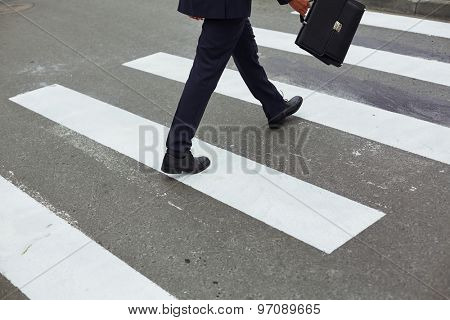 Rear view of businessman with briefcase crossing road