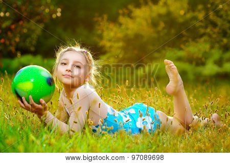 outdoor portrait of young cute little girl gymnast training with ball on grass