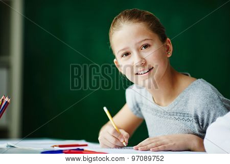 Portrait of cute schoolgirl looking at camera while drawing