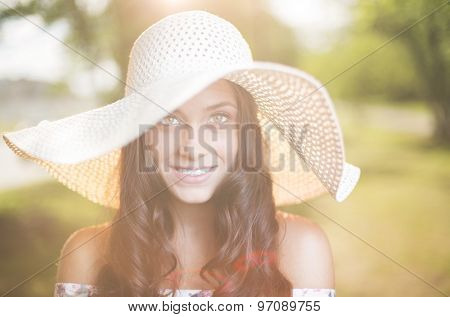 Elegant female in hat looking at camera on sunny day