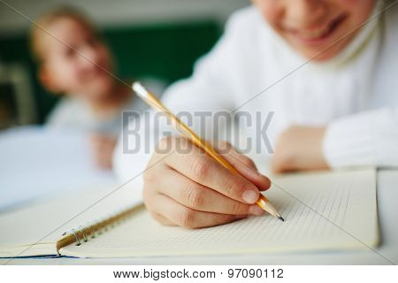 Kid holding pencil and drawing in notepad