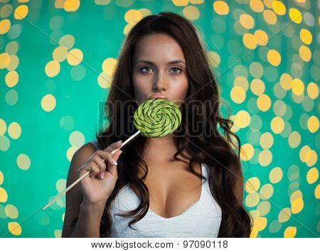 Pretty girl with beautiful long hair licking lollipop and looking at camera