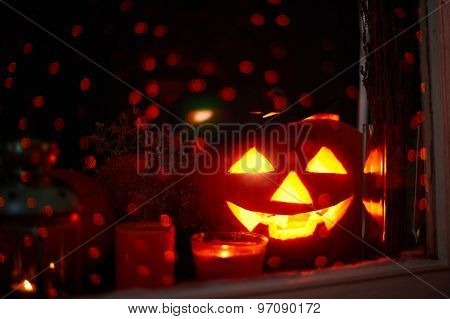 Jack-o-lantern and candles on sparkling background