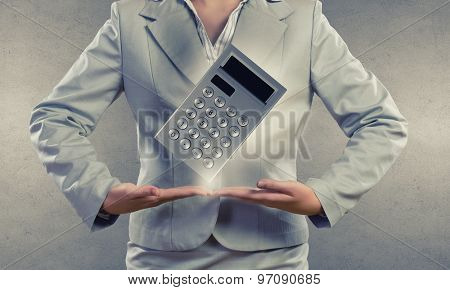 Close up of businesswoman holding in hands calculator