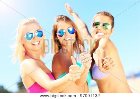 A picture of a group of women showing ok signs on the beach