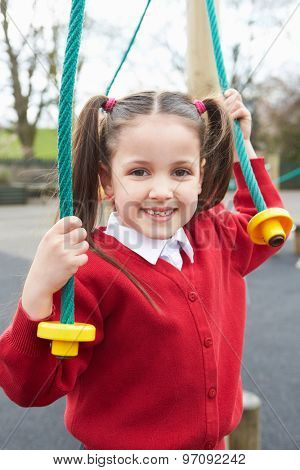 Girl Playing On Climbing Frame In School Playground
