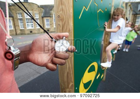 Children On Climbing Wall In School Physical Education Class