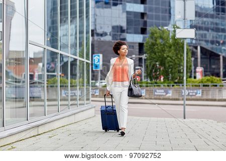 travel, business trip, people and tourism concept - young african american  woman with travel bag walking down city street