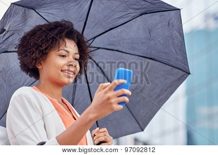 business, bad weather and people and concept - happy african american businesswoman with umbrella texting on smartphone at city street
