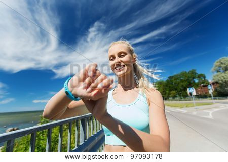 fitness, sport, people, technology and healthy lifestyle concept - smiling young woman with heart rate watch and earphones exercising outdoors