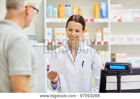medicine, pharmaceutics, health care and people concept - pharmacist reading prescription and senior man at drugstore cash register