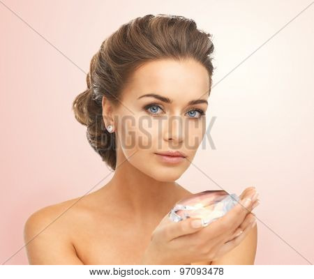 close-up of beautiful woman with earrings showing big diamond