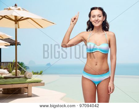 people, travel, swimwear, summer and beach concept - happy young woman in bikini swimsuit pointing finger up to something imaginary over infinity edge pool at hotel resort background