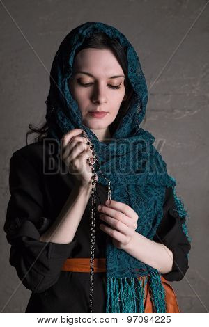 Catholic woman praying with a rosary. Russian woman dressed black and praying