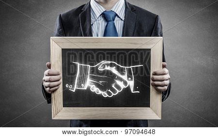 Close up of businessman holding wooden frame with partnership concept