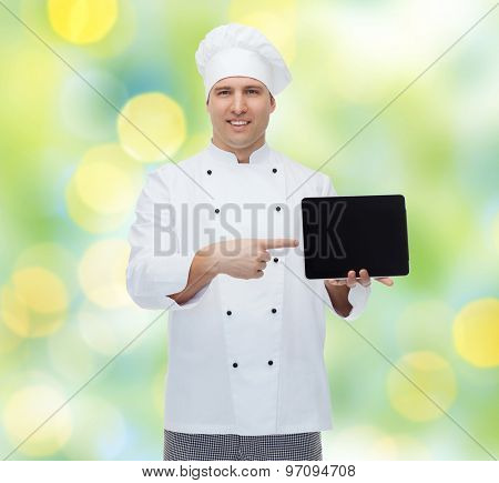 cooking, profession and people concept - happy male chef cook showing tablet pc computer black blank screen over green lights background