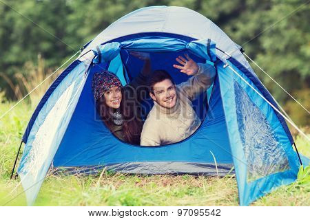 camping, travel, tourism, hike and people concept - smiling couple of tourists looking out from tent and waving hands