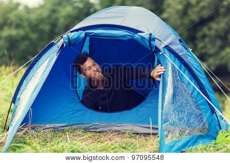camping, travel, tourism, hike and people concept - smiling male tourist with beard in tent