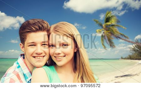 holidays, vacation, love and people concept - smiling teenage couple hugging over tropical beach background