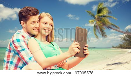 vacation, holidays, travel, technology and love concept - smiling couple with tablet pc computer taking selfie over tropical beach background