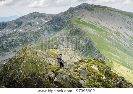 Young woman with backpack do summer hiking in the mountains. Retezat, Carpathians, Romania.