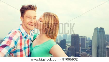 travel, tourism, summer vacation, technology and love concept - happy couple taking selfie with smartphone or camera and kissing over city background