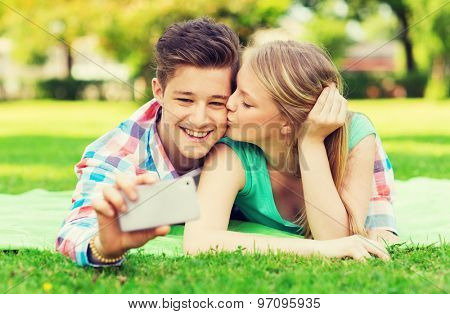 vacation, holidays, technology, love and friendship concept - kissing couple lying on blanket and making selfie with smartphone in park