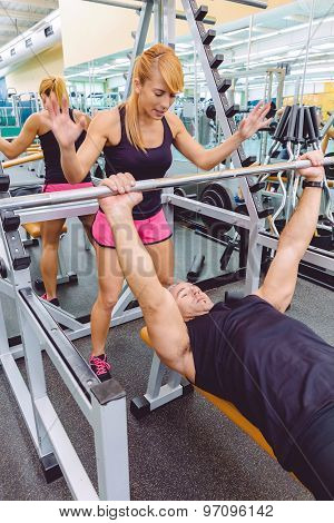 Woman coach encouraging to man in bench press training