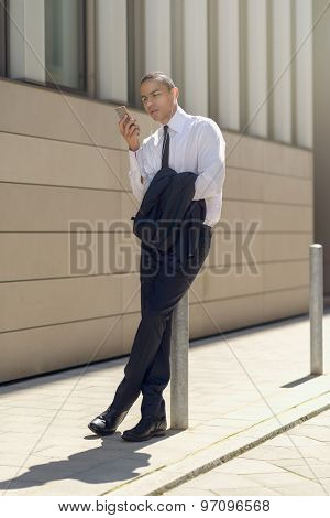 Businessman Sitting On A Bollard Reading An Sms